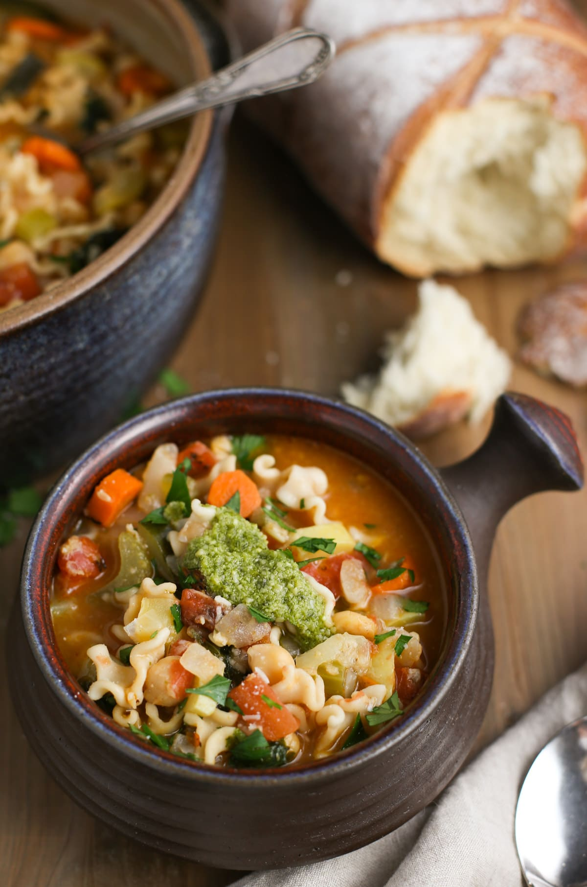 Mighty Minestrone bowl topped with basil pesto and fresh Parmesan cheese with torn bread pieces in background