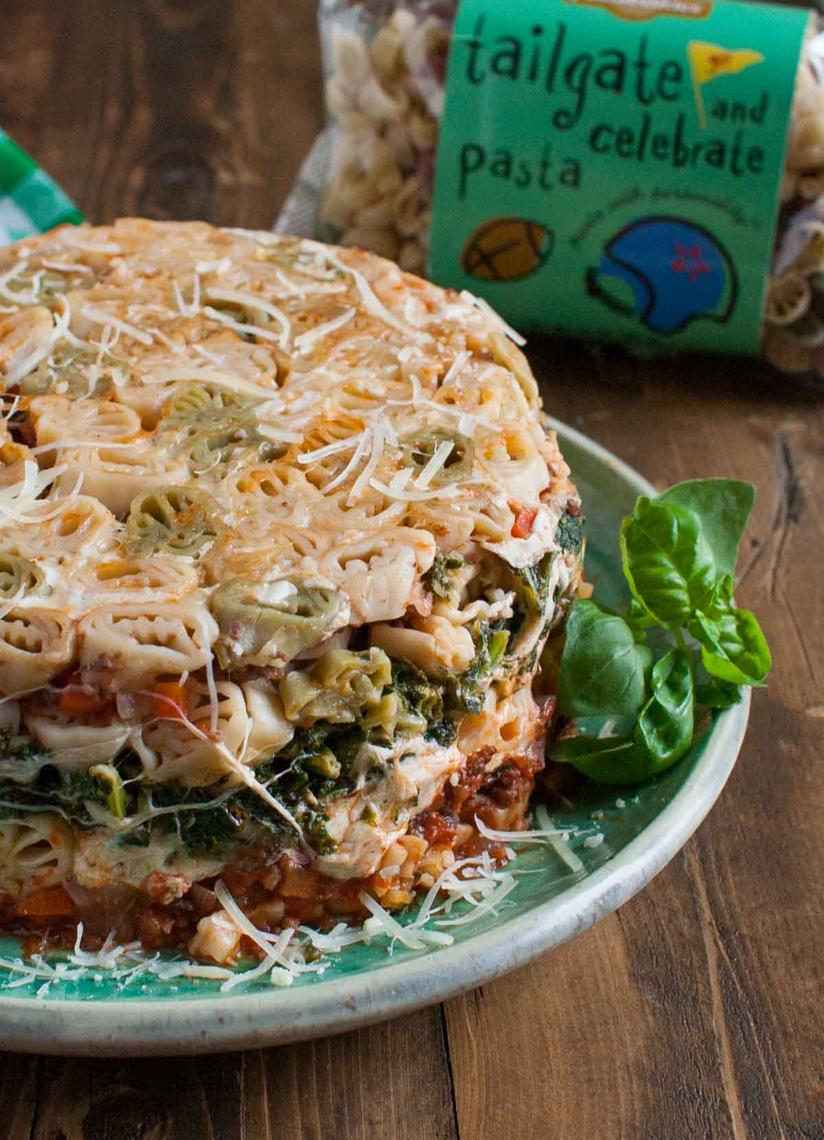 Tailgate Timballo | WorldofPastabilities.com | Nine layers of fabulous flavors: meat sauce, kale bechamel, fresh cheeses, and pasta. Serve slices during the big games and WOW your guests! Fun with any shaped pasta!